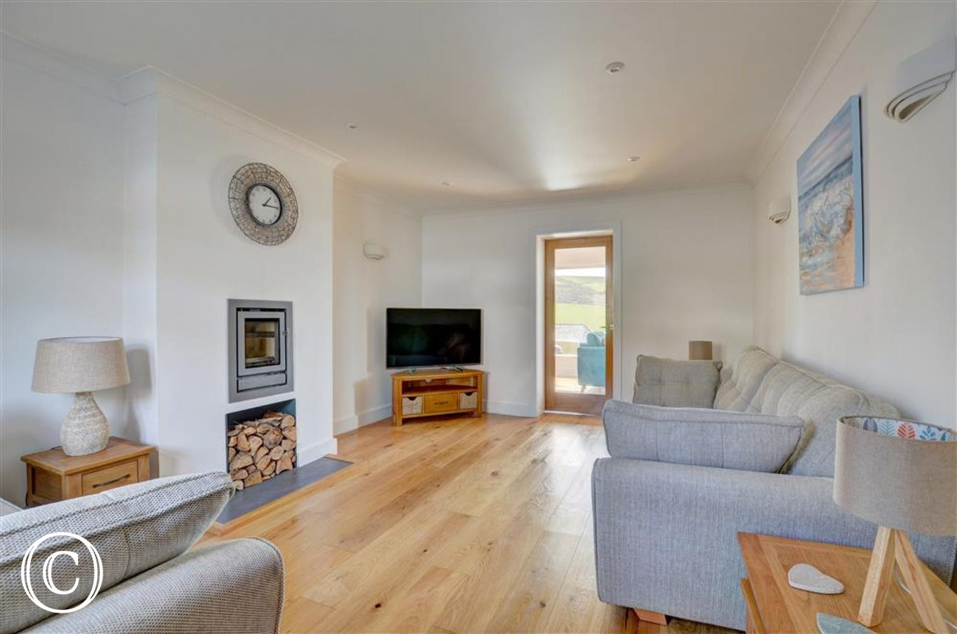Large TV, comfortable seating and cosy woodburner in the sitting room