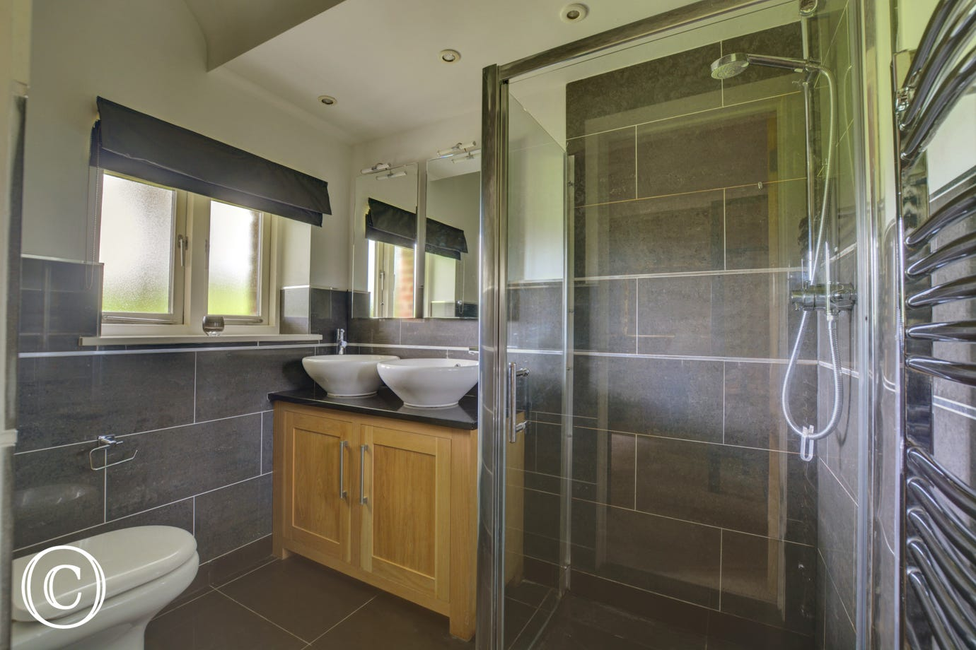 En-suite with twin washbasin, shower cubicle and wc